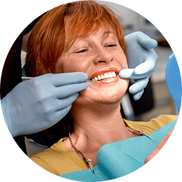 Older woman in dental chair examining smile