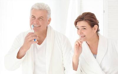 Older man and woman brushing teeth together
