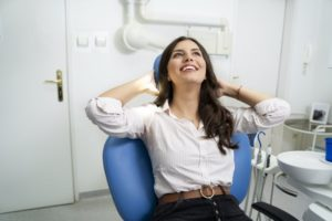 Woman smiling after maximizing her dental insurance