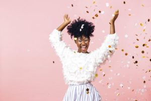 Woman with New Year's resolutions for healthy smile throws confetti