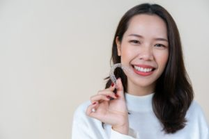 Woman smiling while holding Invisalign clear aligner