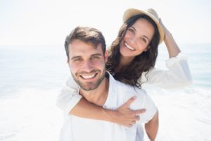 couple on the beach showing off their smiles after seeing a cosmetic dentist in Washington